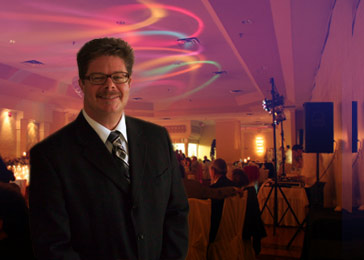 Image for About Us page showing Drew in a suit with a sophisticated party in the background.